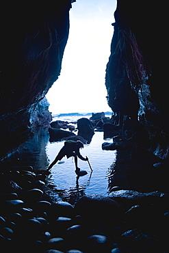 Teenage boy exploring care with rocks in La Jolla, California