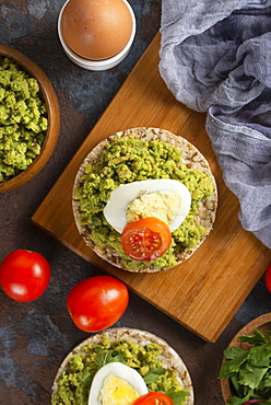 Avocado with egg and tomato on rice cakes