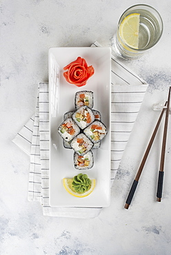 Plate of sushi with chopsticks and drinking glass