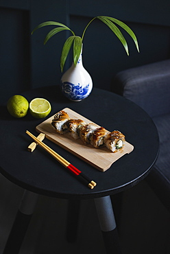 Sushi on table with chopsticks, vase and lime