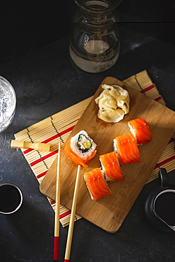 Salmon sushi on cutting board with pickled ginger and chopsticks