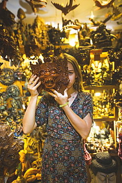 Young woman holding Barong mask in store in Bali, Indonesia