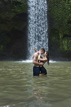 Young couple embracing in river by Tibumana Waterfall in Bali, Indonesia