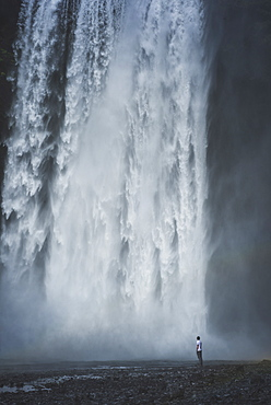 Man standing by Skogafoss waterfall in Iceland