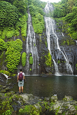 Man standing by waterfall in Bali, Indonesia