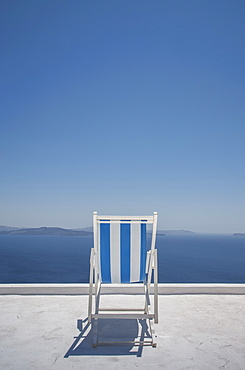 Striped deck chair on balcony by sea in Santorini, Cyclades Islands, Greece