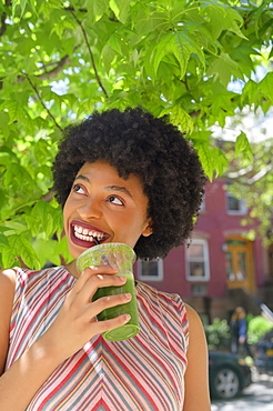 Woman drinking green juice under tree