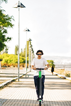 Young man using electric scooter on sidewalk