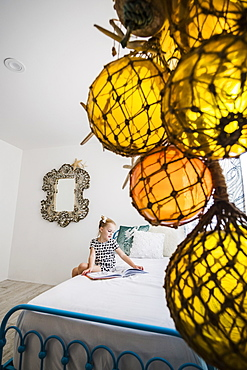 Girl reading book on bed behind decorations