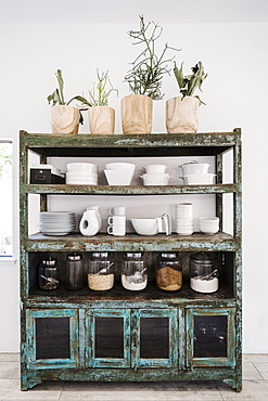 Worn shelves holding tableware, food and potted plants