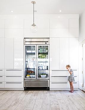 Girl opening drawer by refrigerator