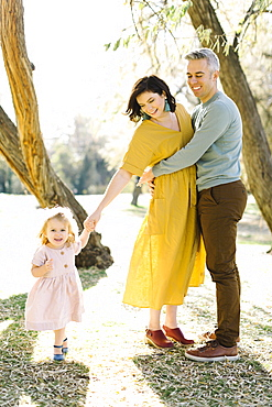 Mid adult couple holding daughter's hand in park
