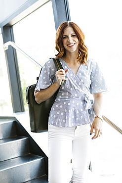 Smiling mid adult woman holding handbag on staircase