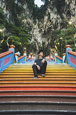 Young man sitting on colorful staircase by cliffs in Kuala Lumpur, Malaysia