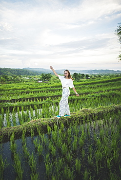 Woman walking in rice paddy in Bali, Indonesia