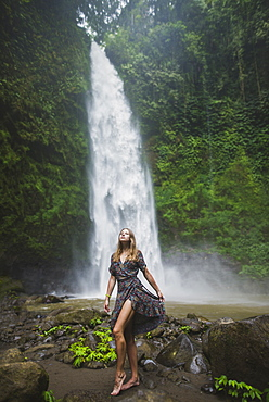 Woman standing by waterfall in Bali, Indonesia