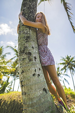 Young woman hugging palm tree in Bali, Indonesia