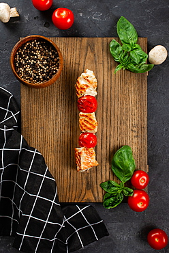 Grilled chicken and tomato skewer on cutting board