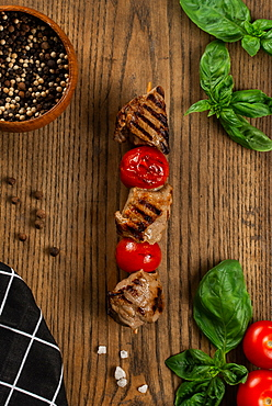 Grilled meat and tomato skewer on cutting board