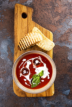 Tomato soup with toast on cutting board