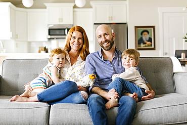 Family smiling on sofa