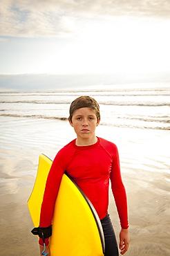 Boy holding body board on beach
