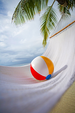 Beach ball on hammock under palm tree in Ari Atoll, Maldives, South Asia