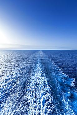 Wake in sea under clear sky