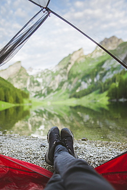 Woman's feet sticking out of tent by Seealpsee lake in Appenzell Alps, Switzerland