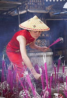 Woman lighting incense in temple in Lijang, Shangri-La Region, Yunnan Province, China