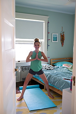 Girl doing yoga in bedroom