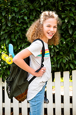 Girl with skateboard in backpack