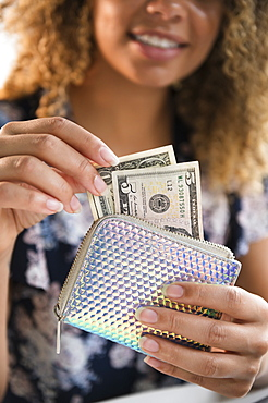 Smiling woman holding wallet with money
