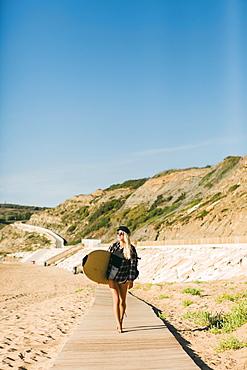 Woman holding surfboard on boardwalk