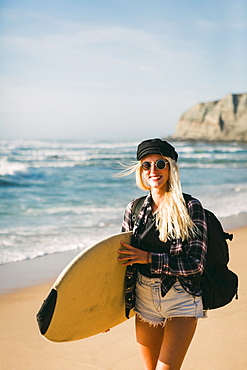 Smiling woman holding surfboard on beach