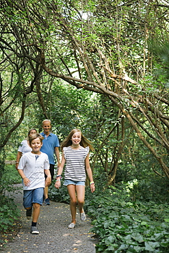 Family walking on path in forest