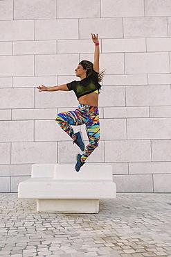 Woman jumping by wall, Lisboa, Lisbon, Portugal