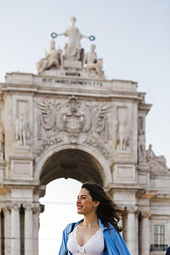 Smiling woman by Rua Augusta Arch in Lisbon, Portugal