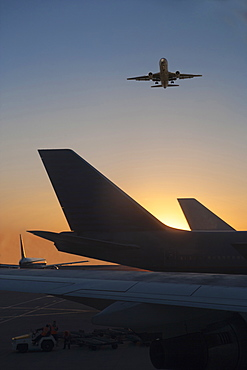 Airplane flying over airplane on runway at sunset, Miami, Florida, USA