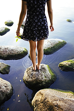 Barefoot woman standing on rock in sea