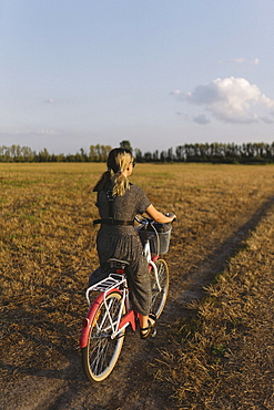 Woman riding bicycle in field, Belarus, Brest