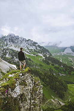 Man on rock by mountains