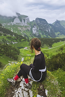 Woman sitting on rock by mountains in Appenzell, Switzerland