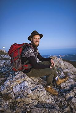 Smiling man sitting on rock at sunset