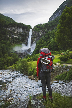 Woman wearing backpack with waterfall in distance