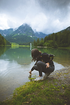 Young woman crouching by lake
