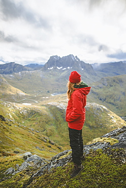 Young woman in red jacket on mountain