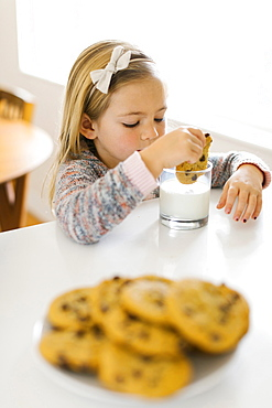 Girl eating milk and cookies