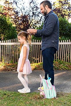 Man tying his daughter's hair in ponytail
