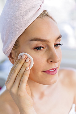 Woman cleaning face with cotton pad